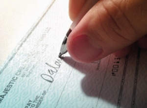 Closeup of a person's hand writing a check